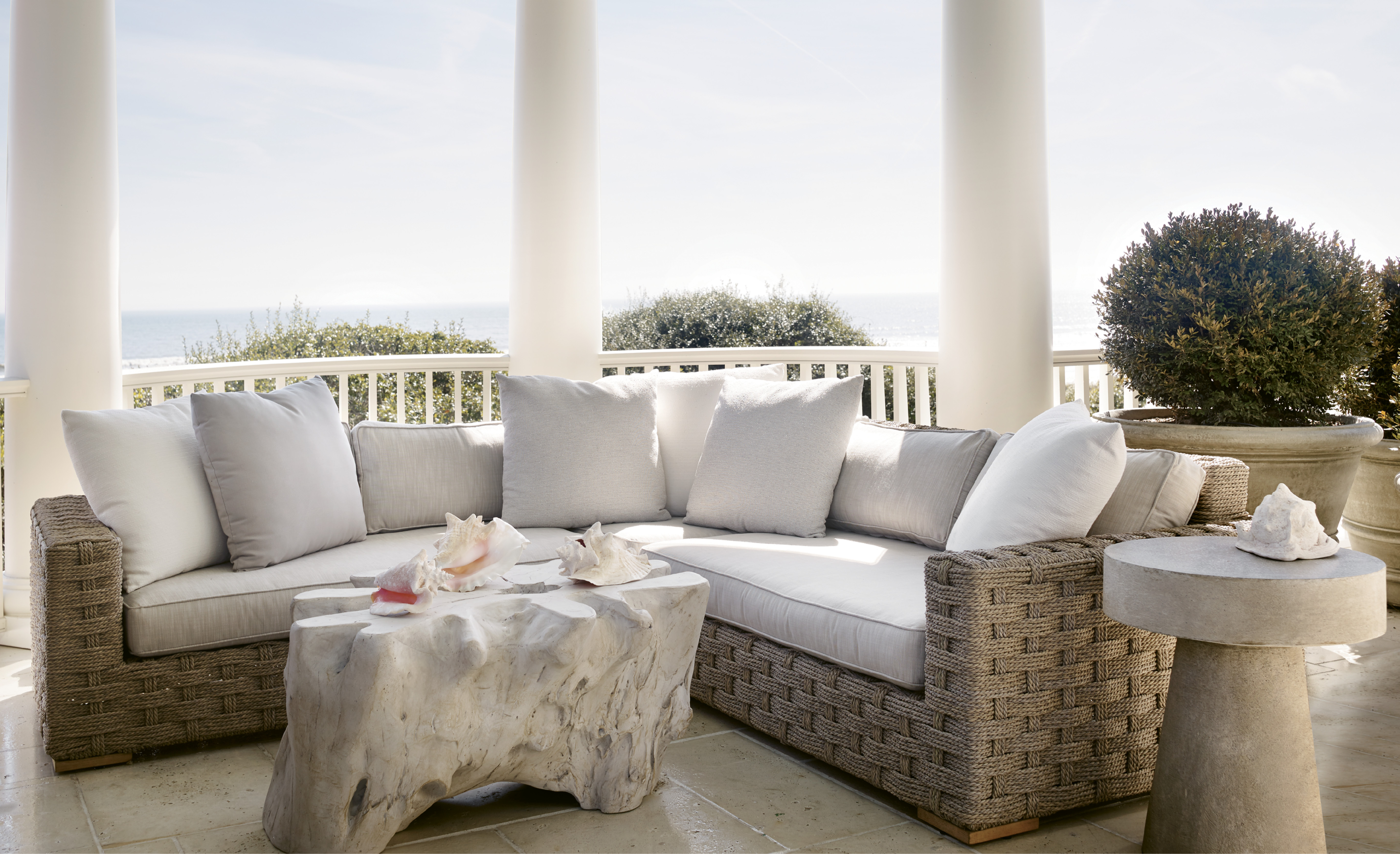 "This columned porch provides both privacy and panoramic views. ""The curved porches and their roofs shield the house from the neighbors, so you feel like you're in the only house on the beach,"" says architect Chris Rose. The outdoor furnishings, including a Restoration Hardware rope sectional, were selected to echo the classicism and Cape Cod influence of the architecture."