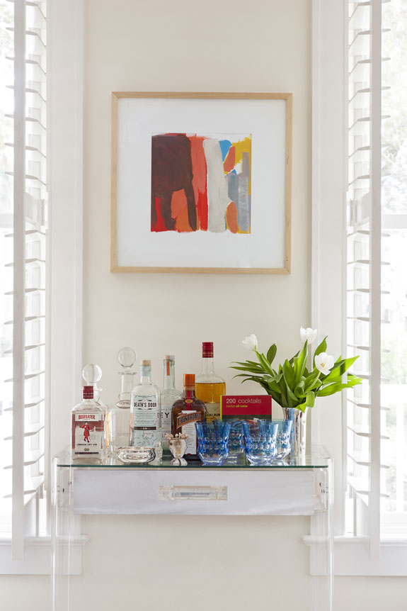 A work by Sally King Benedict helps the mini bar stand out visually against a neutral wall.