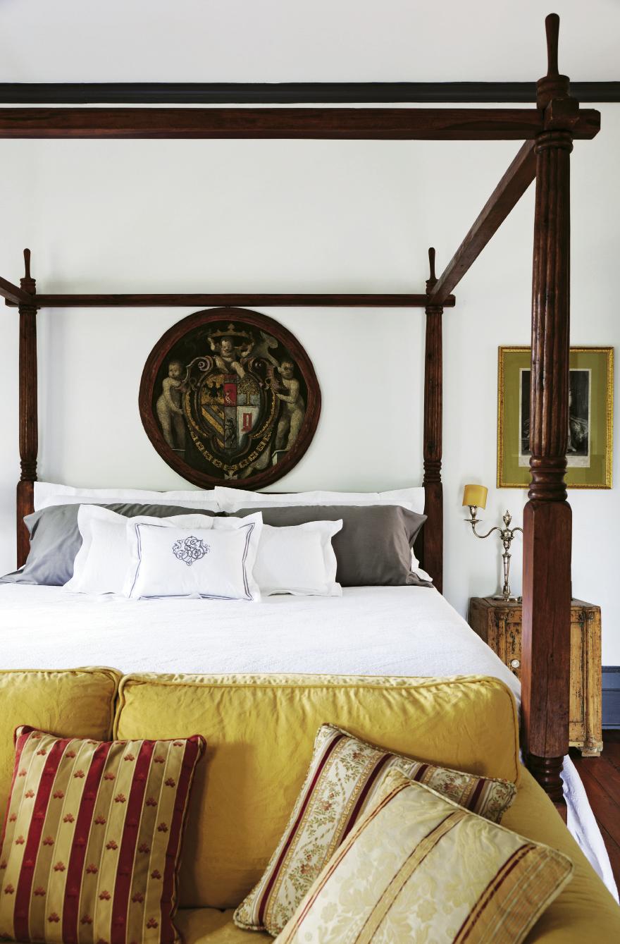 An Indonesian four-poster bed and the della Porta family crest on canvas in the master bedroom