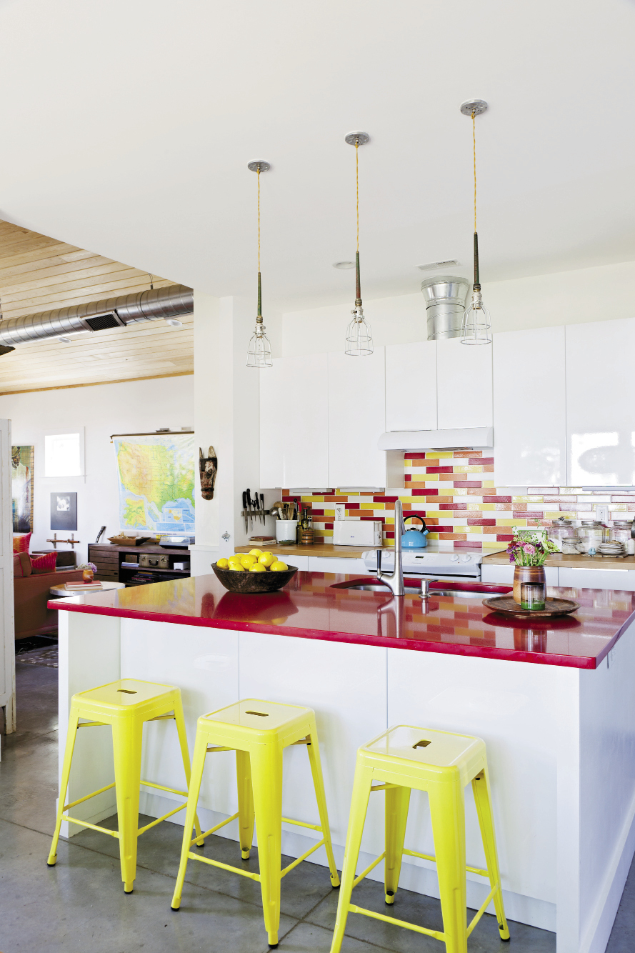 Yellow aluminum stools, a sparkly red quartz counter top, and a vibrant tile backsplash add doses of color to the kitchen.