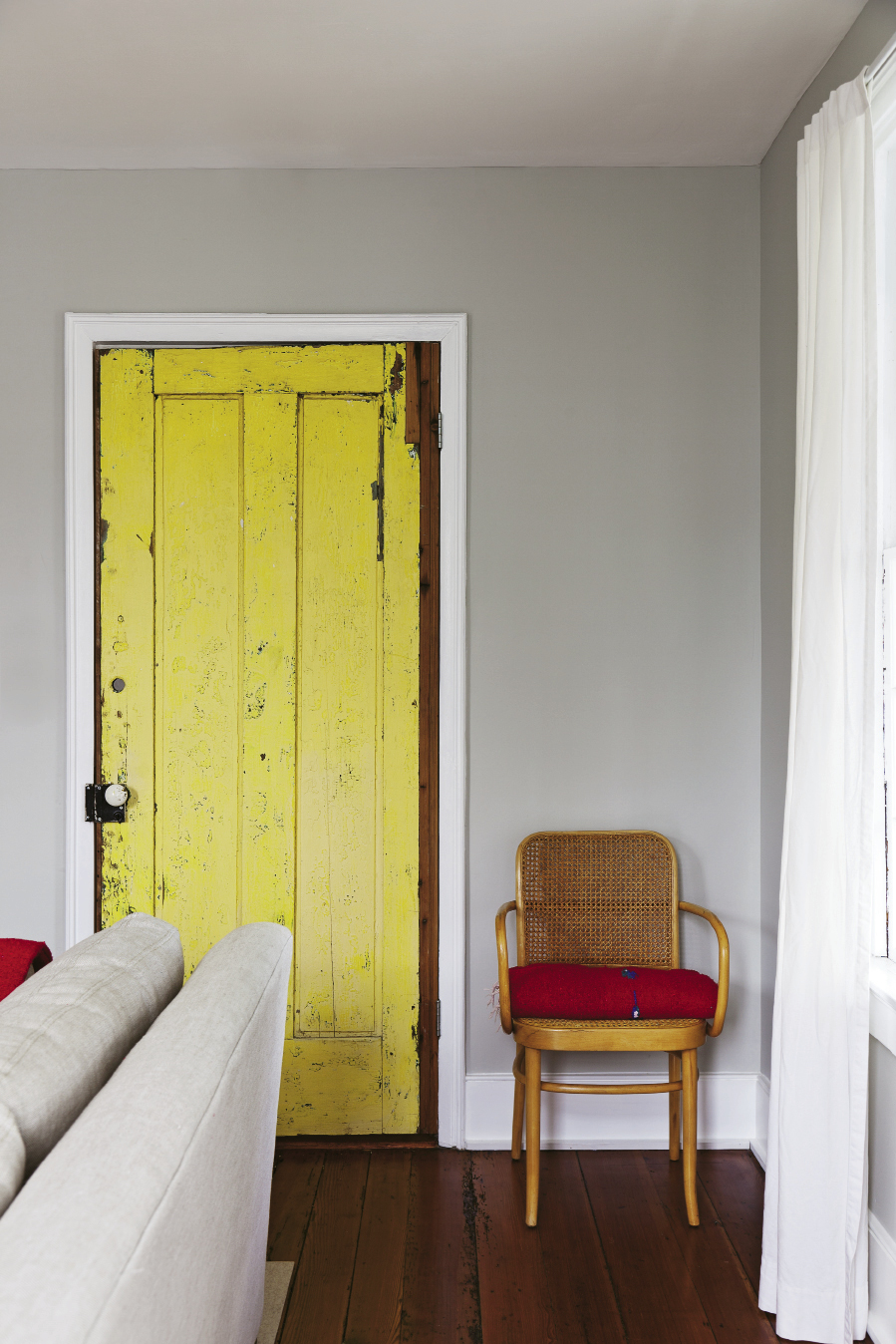 When the couple bought the building, this heart-pine door, originally the home's back entry, was painted bright yellow. It's been cleaned up and brought inside, but vestiges of the sunny paint color remain.