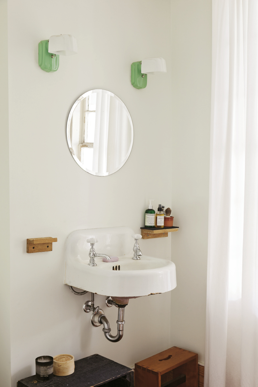 In the bath, retro-inspired sconces suit the original sink.