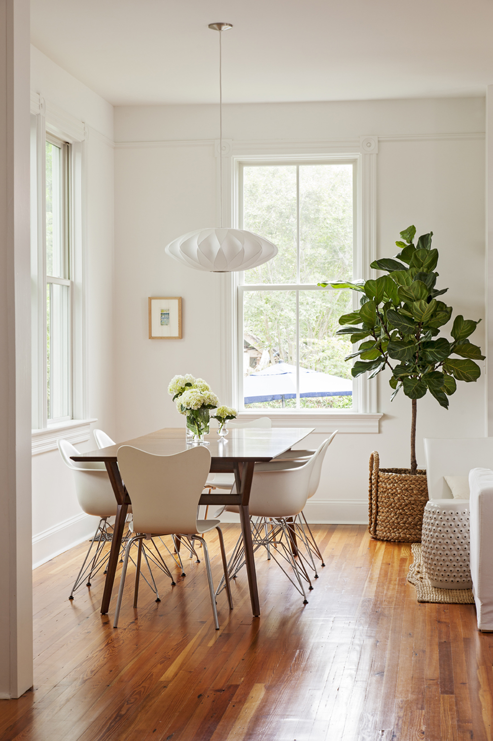 Modern History: In the addition, custom-milled trim and reclaimed floors reference the home's original architecture, while midcentury furnishings, such as Eames dining chairs and a George Nelson light fixture, set a contemporary tone.