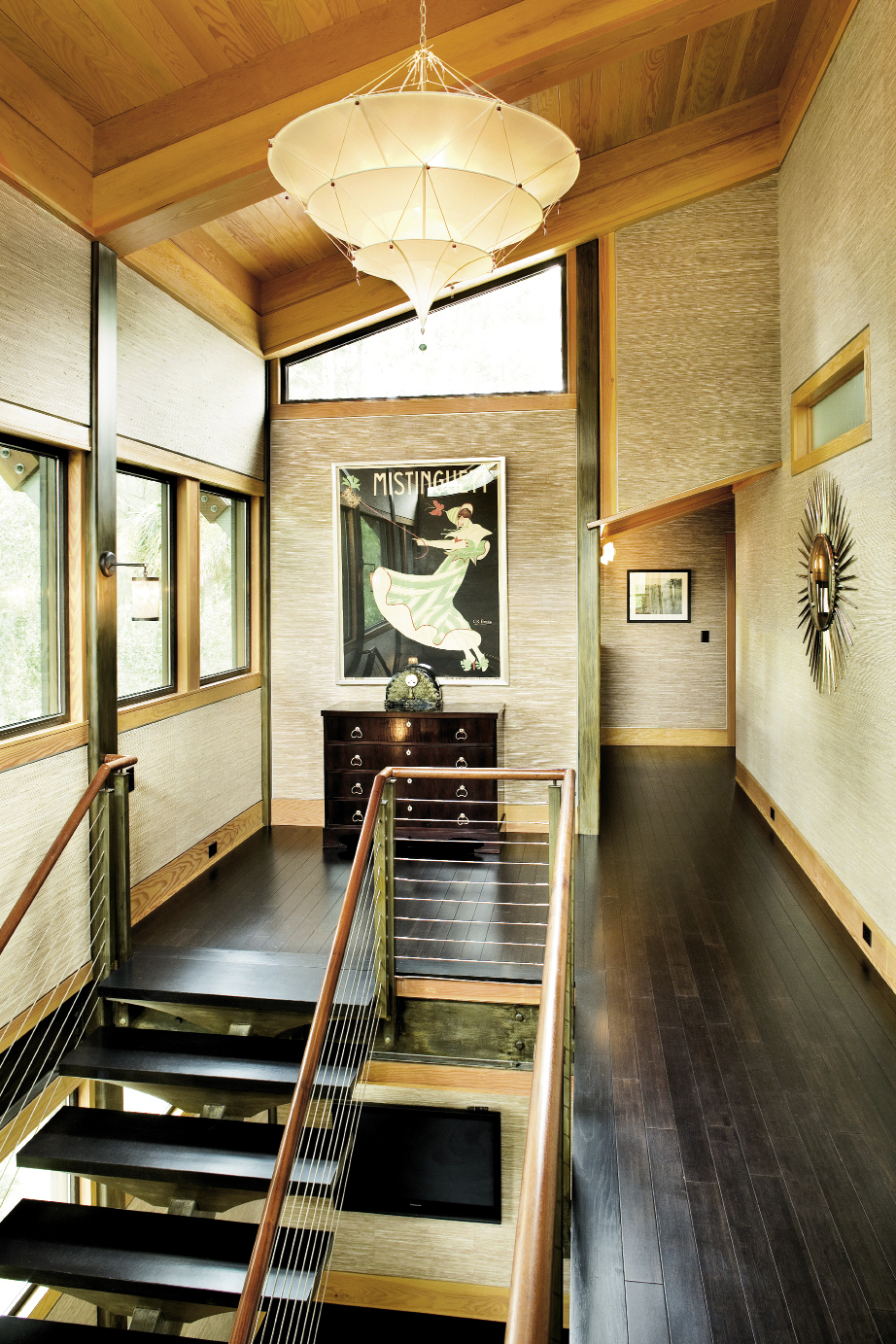 A bank of windows and a Fortuny  pendant shade ensure the upstairs hall—with its angled roofline—receives ample light.