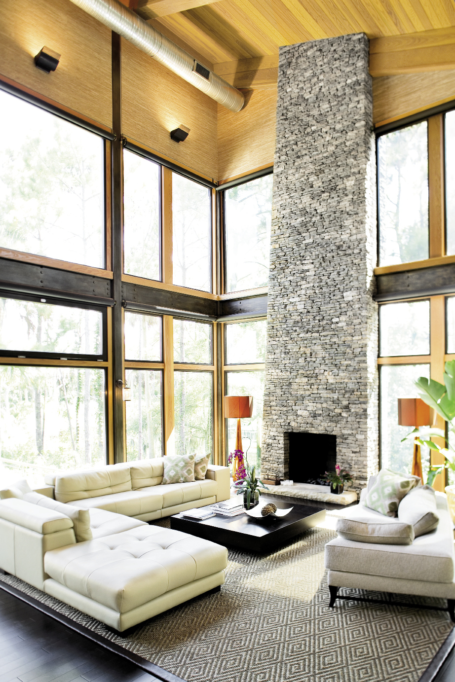 Chris opted to keep the home's sturdy steel framing exposed in the lofty great  room, which features a 27-foot stacked  stone