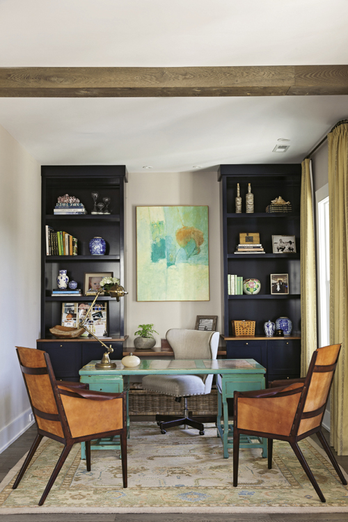 Office Space: Navy bookshelves of Bishop's own design provide practical storage in the home office; a painting by an unknown artist inspired the nook's turquoise and orange palette.