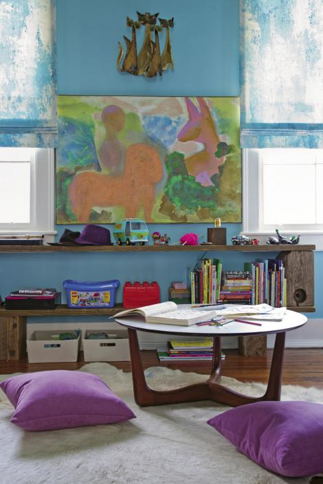 In Loulou and Sasha's room, a Danish Rosewood coffee table with laminate top, a cowhide rug, and low shelving create a comfy kids' work area.