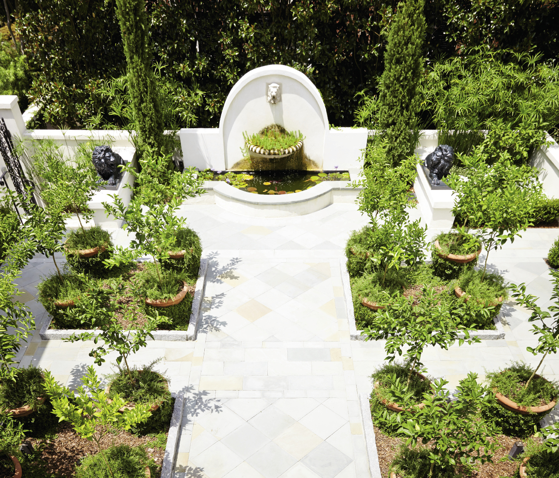 Landscape architect Sheila Wertimer replaced a shallow pool with a classic courtyard, featuring large pots of citrus and rosemary framing a centerpiece fountain.