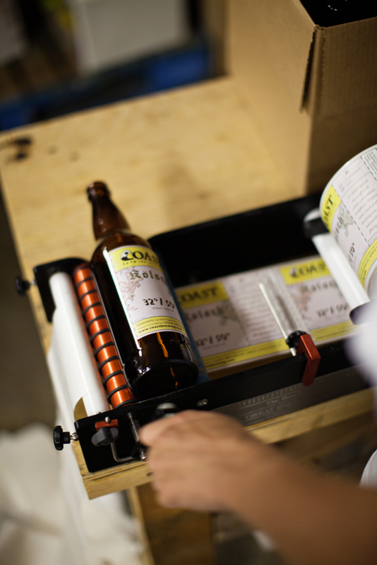 COAST's labeling machine. They label one bottle at a time.