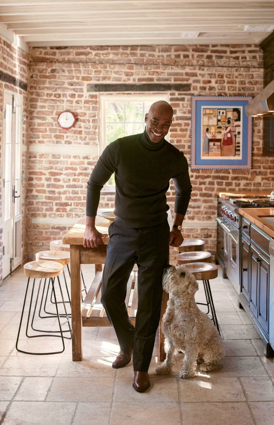 The physician, shown with his pup, Kasey, worked with interior stylist Nathalie Naylor to balance his love of modernism with the home's traditional architecture.