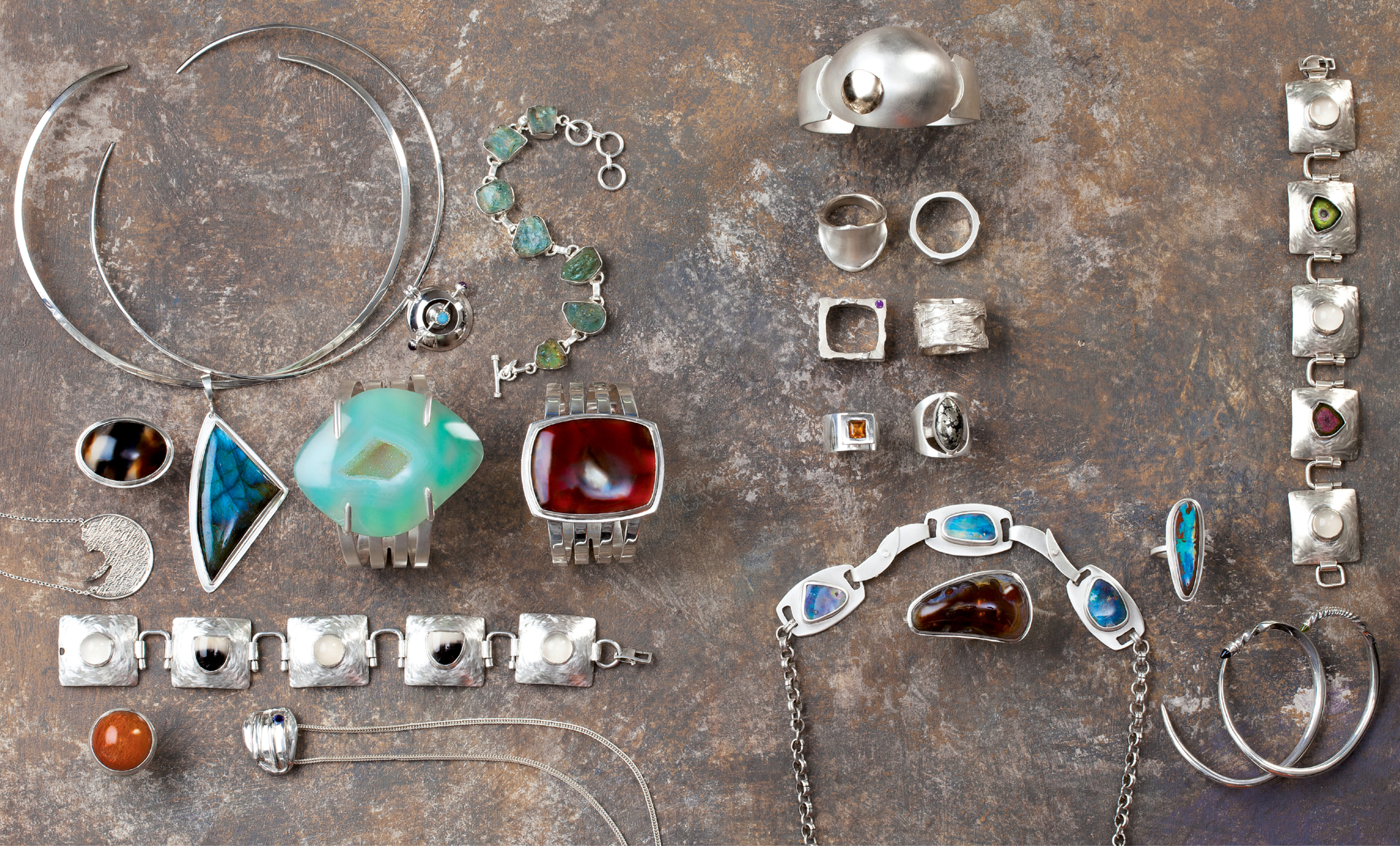 """Angela Hall, Angela Hall Designs: Intriguing gemstones often drive the clean-lined designs of the College of Charleston grad, who continued her arts education at Savannah College of Art and Design, The Museum School of Fine Arts in Boston, and the Haystack School in Maine and launched her eponymous custom jewelry line in Charleston in 2000. Whether starting with Australian boulder opal, Brazilian piranha agate, sapphire, or watermelon tourmaline, she incorporates techniques in fine metals—forming, soldering, filing, piercing, reticulation, and casting—to create each piece. """"My work embodies simplicity and a respect for the fundamental principles of design,"""" she explains. See her jewelry at Charleston Farmers Market, as well as at angelahall.net and angelahall1.etsy.com."""