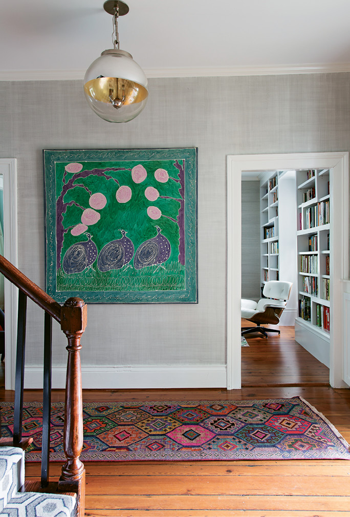 BOLD ACCENTS: Grasscloth wallpaper provides a neutral backdrop for the foyer's bright silk painting and two patterned rugs.