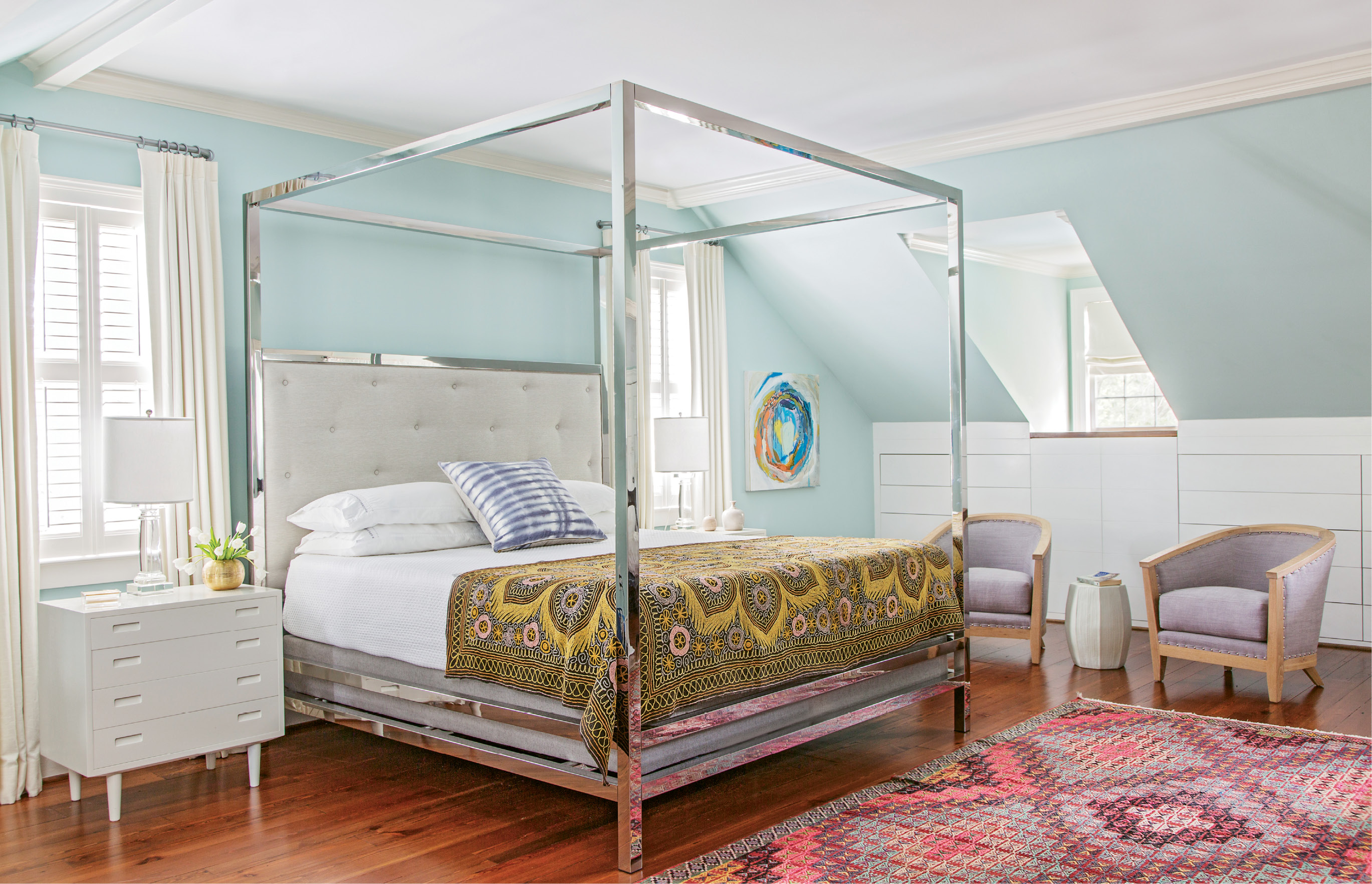 In the master bedroom, vintage textiles and mid-century nightstands add depth and texture to a streamlined canopy bed