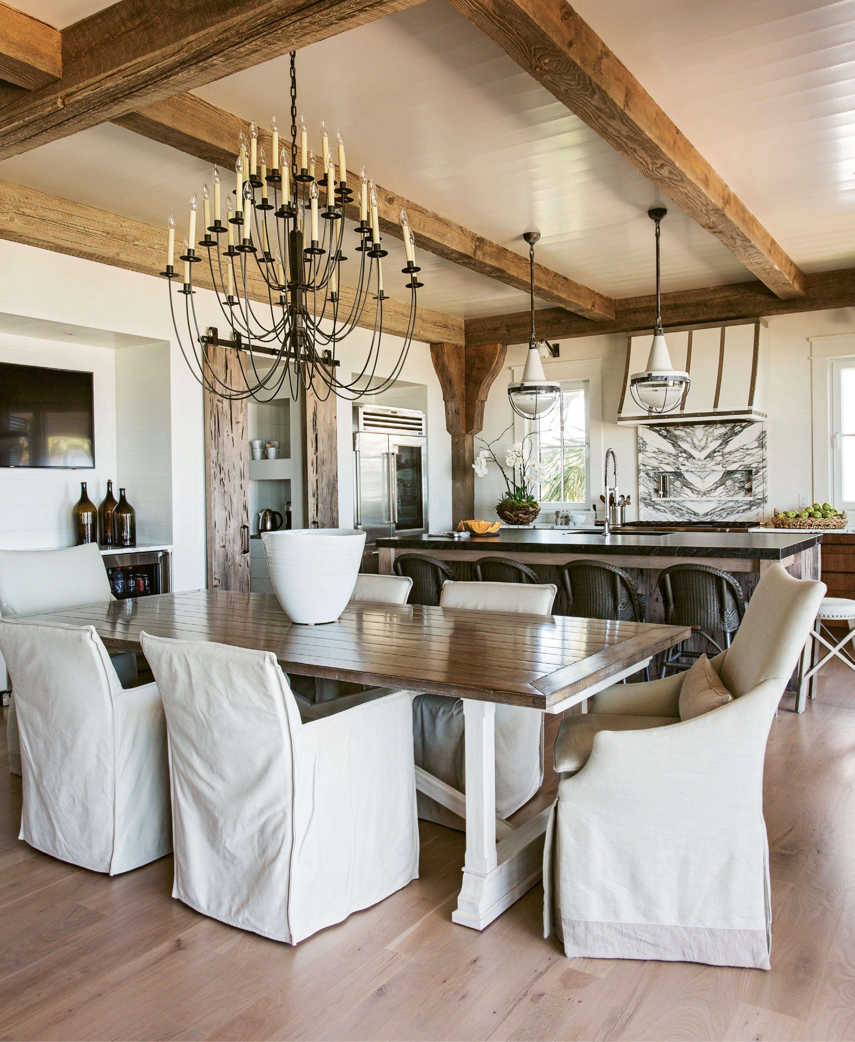 White leather chairs by Lee Industries flank the kitchen table, which can expand to accommodate 14.