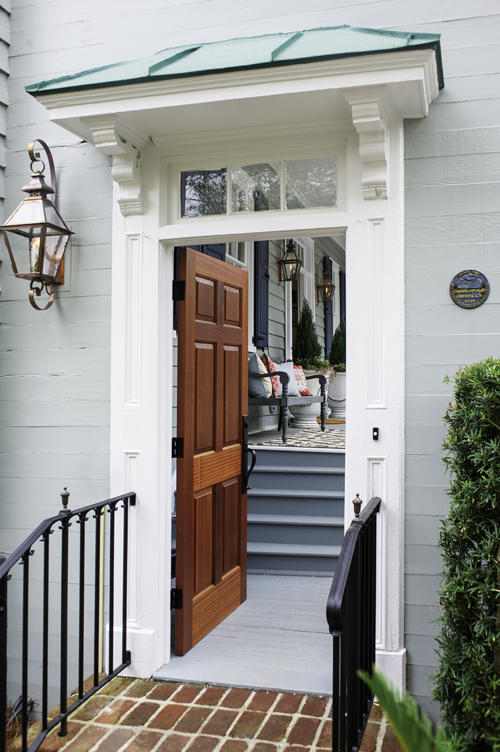 A natural mahogany front door sets off the entry's white moulding and transom.