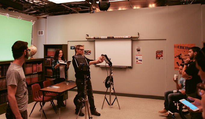 "Bryan Curb (center) directs a shot inside ""Jamestown University."""