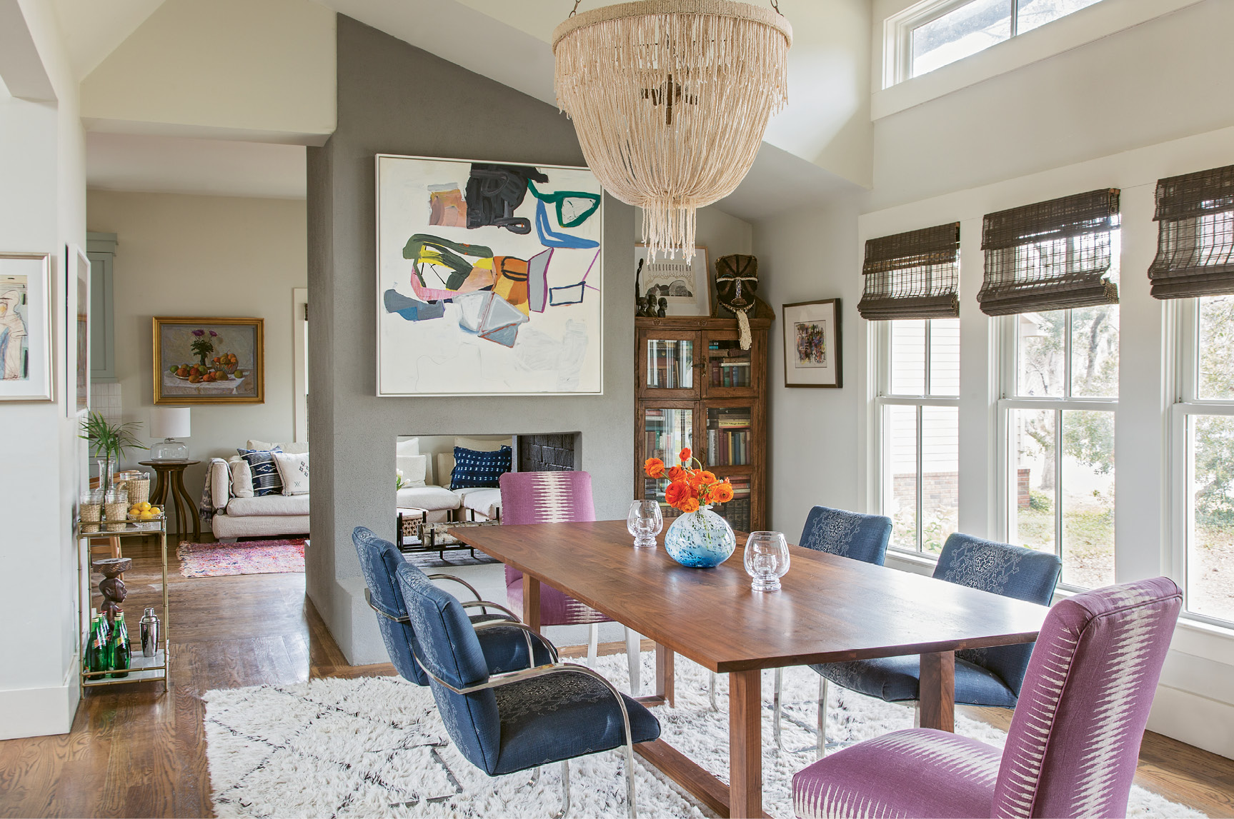 ...the slipper chairs on either end of the dining table were handed down from a friend and recovered in a fresh fabric, and the rest of the dining chairs were scored on eBay. An abstract painting by Brian Coleman adds a dash of color and texture above the wraparound fireplace, which was stuccoed during the renovation for a more modern, streamlined look.