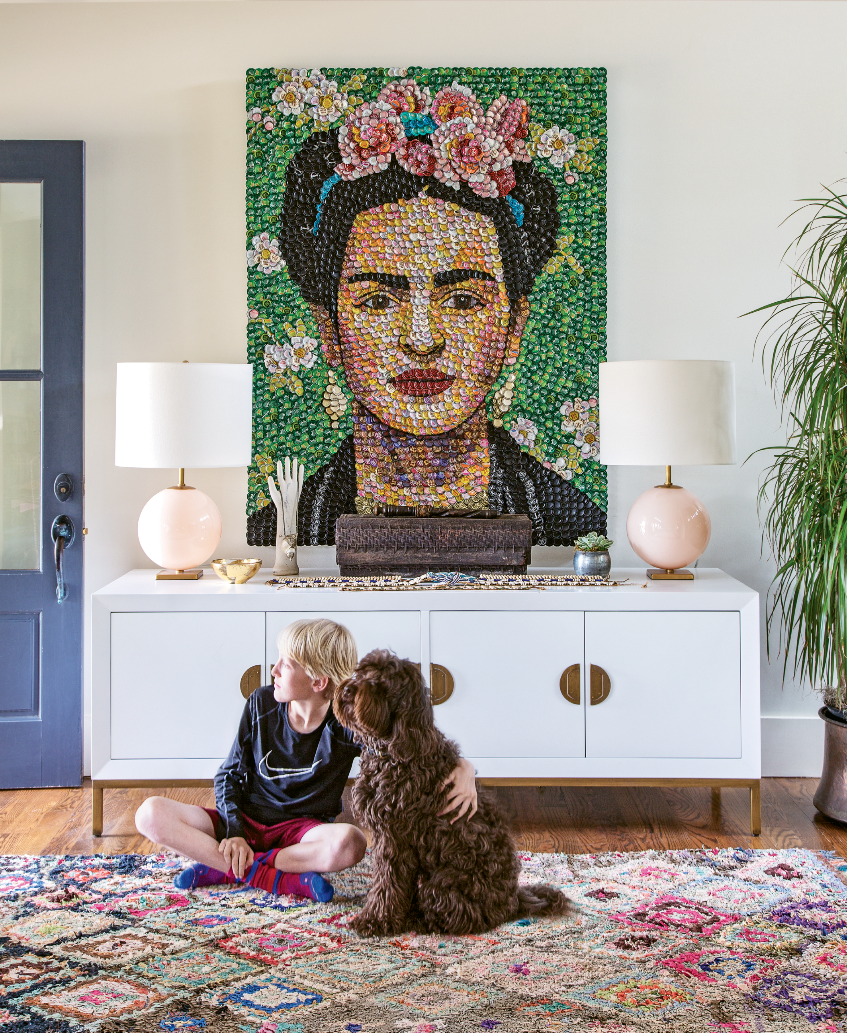 "Captivating Entry: Colorful and joy-filled artwork, like this bottle-cap portrait of Frida Kahlo by area artist Molly B. Right, jives well with the Williamsons' lively home, as does the open floor plan. ""The boys are so dynamic; the level of activity here is insane,"" says Allison."