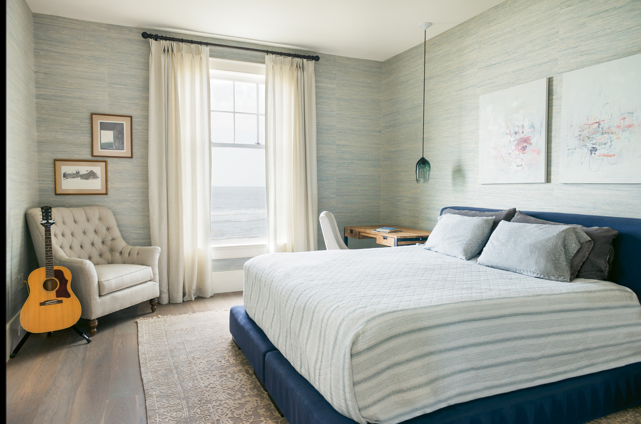 In the master bedroom, modern touches, such as paintings by Tim Hussey, commingle with traditional pieces, like a tufted club chair.