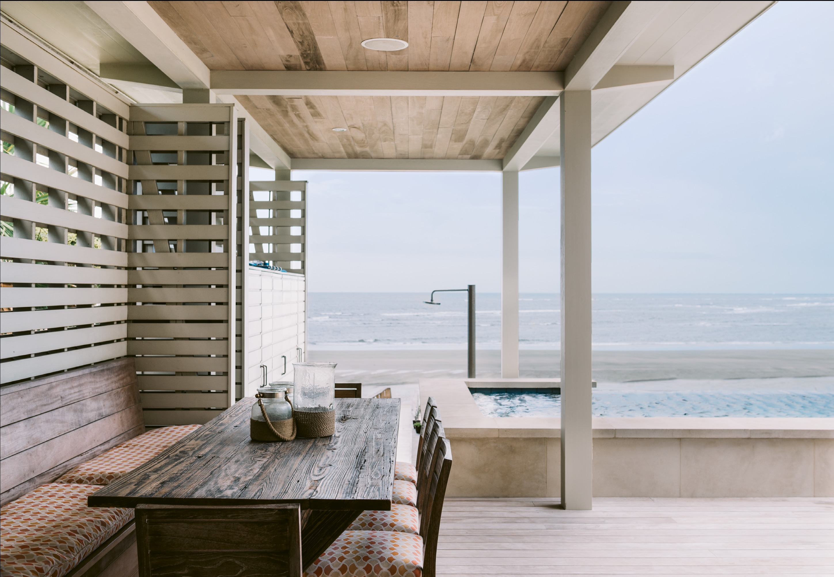 """On the elevated courtyard, a slatted wall serves as a privacy screen while allowing breezes to flow through. """"We eat out there as much as possible,"""" says Suzanne of the outdoor dining area with a large reclaimed wood table crafted by Landrum Tables. """"We can enjoy a glass of wine while the kids are swimming."""""""