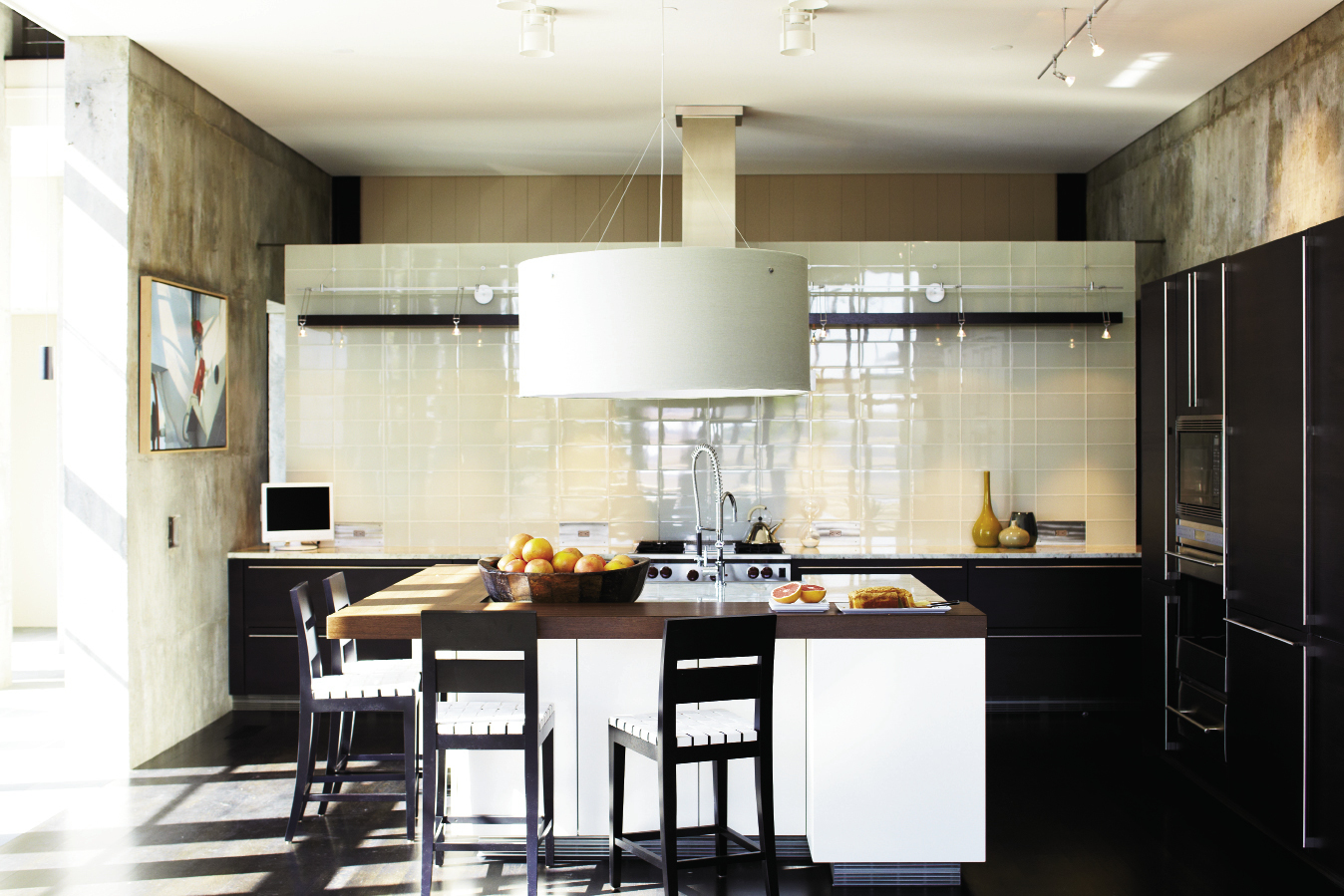 Island Living: The Siematic-designed kitchen features wenge cabinetry and woodwork and a large round shade pendant; a floating wall of light green glass subway tiles offers a cool and contemporary backdrop.