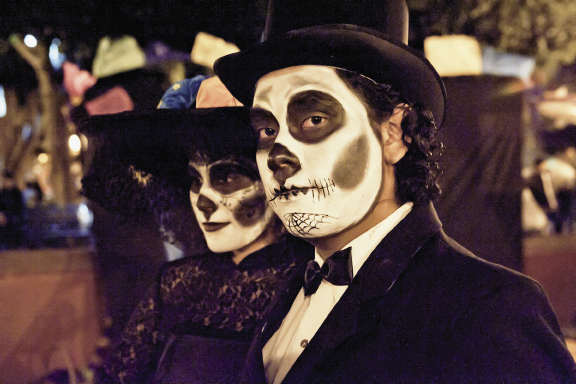 the Day of the Dead brings out revelers in dramatic attire to honor their ancestors.