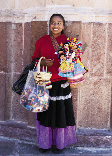 A local girl sells her handmade dolls in El Jardín.