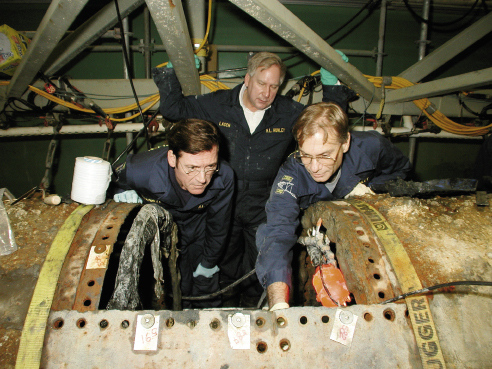 With Warren Lasch, former chairman of Friends of the Hunley, and Dr. Robert Neyland, then Hunley Project director, peering into the interior of the historic submarine in 2001