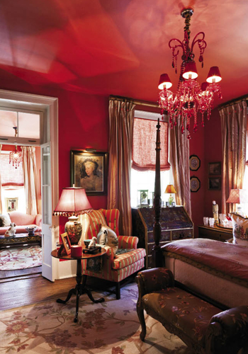 """Throughout the house, we wanted color that resonates happiness and daring,"" says Juan. The second-floor guest suite in the main house is saturated in a fiery shade Juan deems ""pimiento"" before buoyantly adding, ""and the chandeliers are bordello red."" Visitors to this ""Scarlet O'Hara Room"" are afforded their own sitting area and a piazza that presents a sweeping view of the garden."