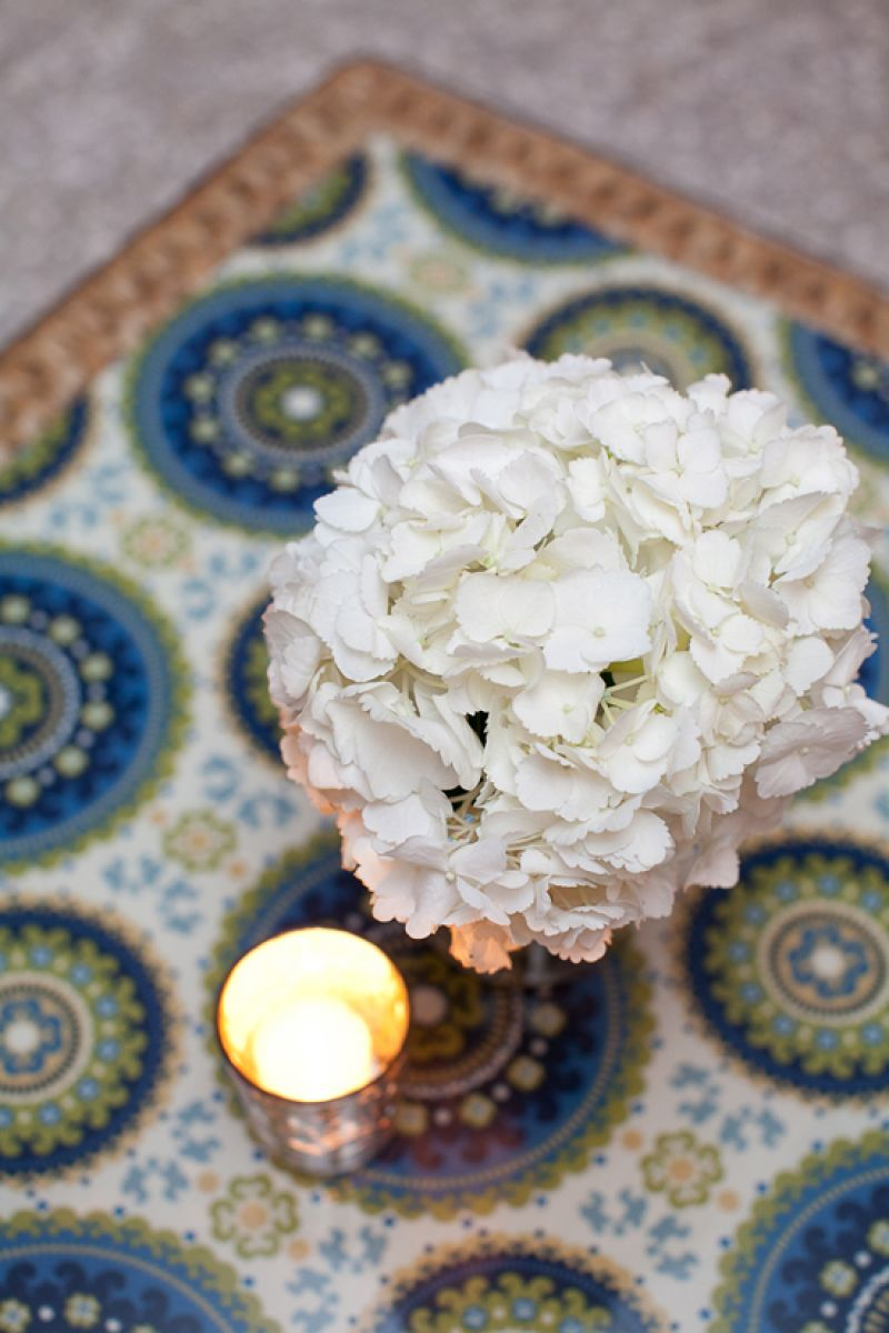 TOP THAT: Lounge tables were topped with the paisley pattern found throughout the reception. Accents were kept simple—white hydrangea and small mercury glass votive holders—as to not compete with the bright design.