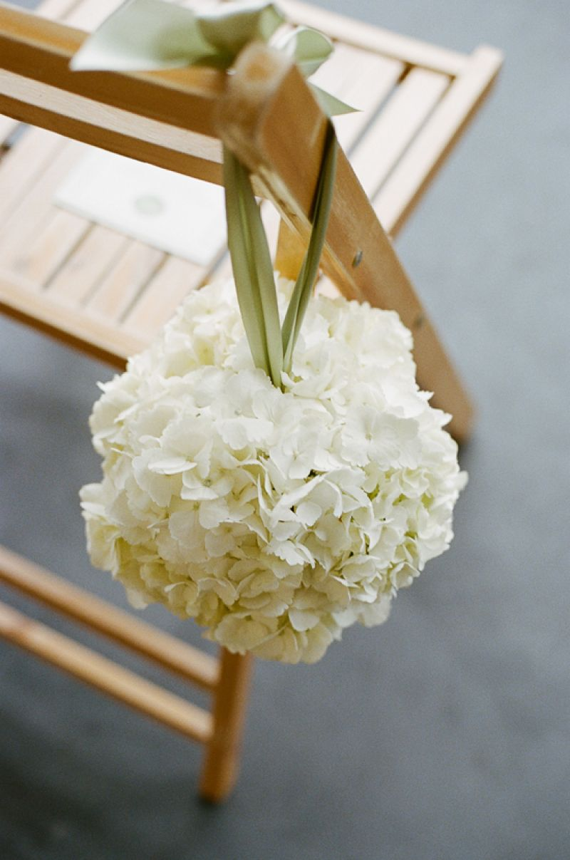TIED ON: Jade Water Designs shaped lush spheres of white and green hydrangea, white peonies, and white ranunculus to accent ceremony seating.