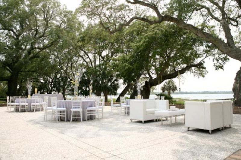 WIDE OPEN SPACES: The terrace at Lowndes Grove overlooks the Ashley river; the oyster tabby suited the pale gray and white reception furniture in sublime fashion.
