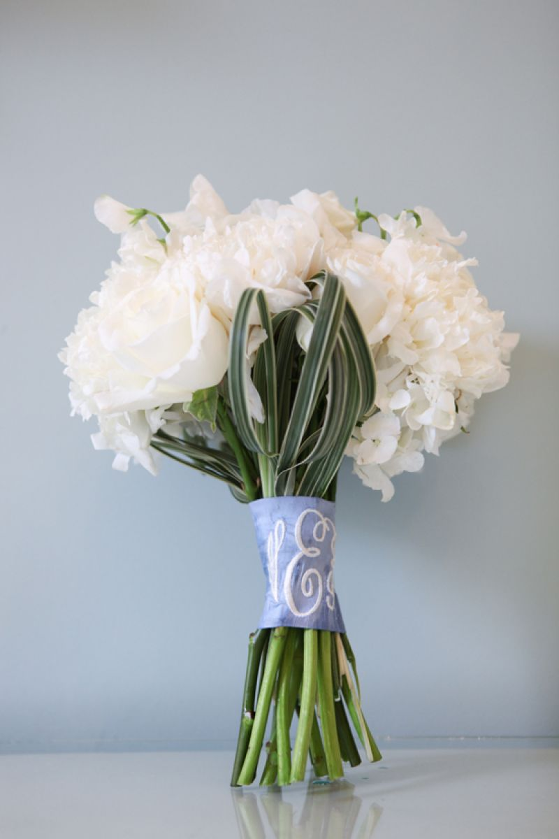 SOMETHING NEW: The bride's white rose and hydrangea boutique was wrapped in a cornflower blue dupioni silk sash embroidered with her new initials.