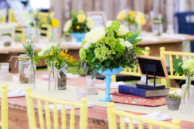 MIXED AND MATCHED: Rather than competing with their bright vessels, the fern fronds, green hydrangea, and yellow peonies of the arrangements complemented the colorful vases.