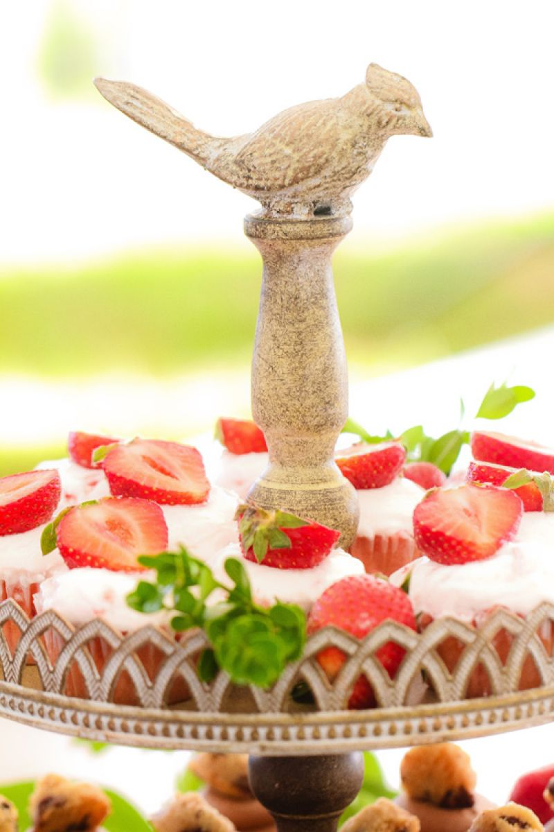 CHARMING CHEWS: Sweet Reba's topped the flavored cupcakes with fresh strawberries. The leafy garnishes and bird-topped stone stand gave the setup a secret garden feel.