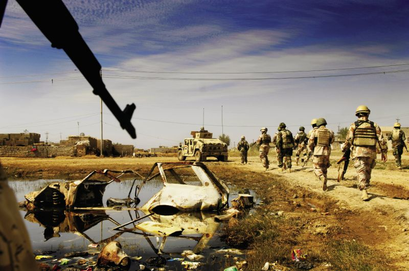 March 4, 2007: Iraqi Army soldiers march past a car destroyed during a prior operation in New Baqubah, Iraq. The operation aimed to eliminate the area as a base for anti-Iraqi forces building I.E.D.s (improvised explosive devices).