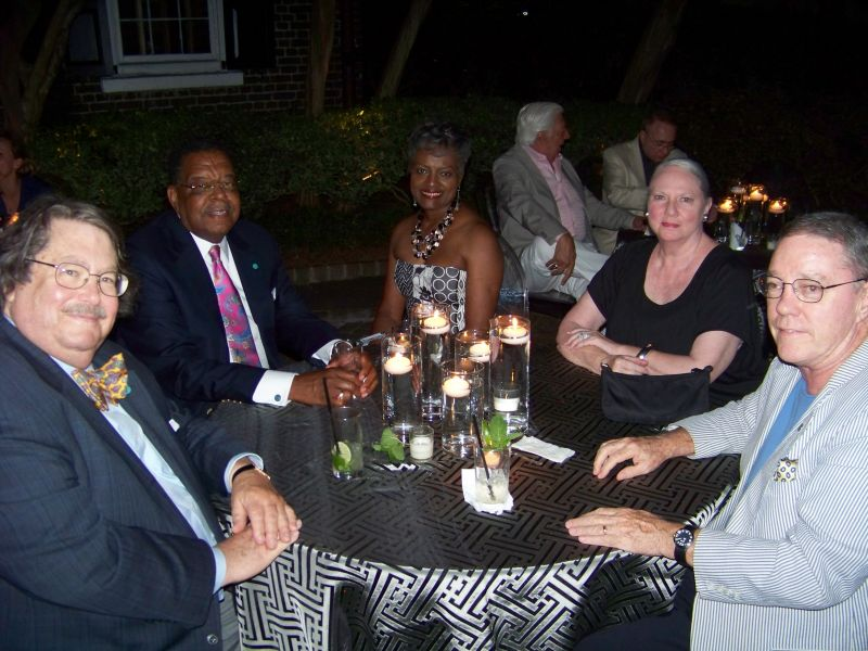 A group of patrons chats in the moonlight.