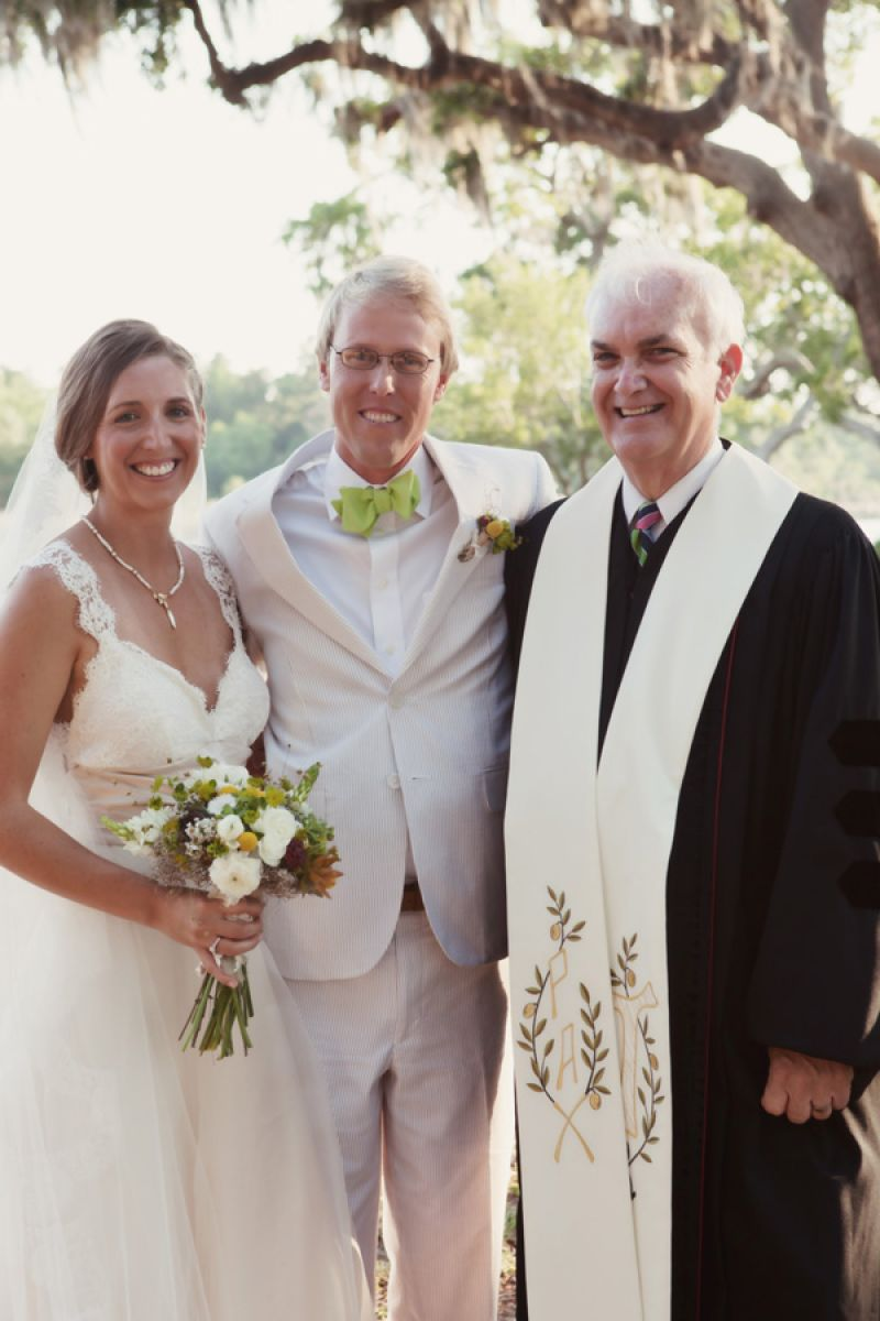 MR. & MRS.: Lindsey and Christopher give off a newlywed glow posing for a picture with the officiant.