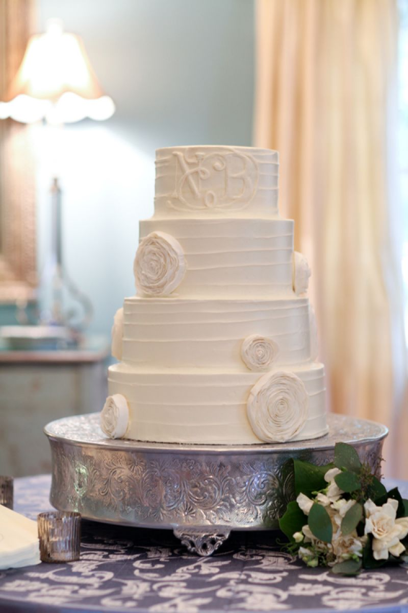 SUGAR RUSH: Ogled at by guests, the four-tiered wedding cake was designed by Lauren Mitterer of WildFlour Pastry and decorated with an edible monogram. The textures of the white confection, the hammered silver cake stand, and the printed linen added depth to the display.