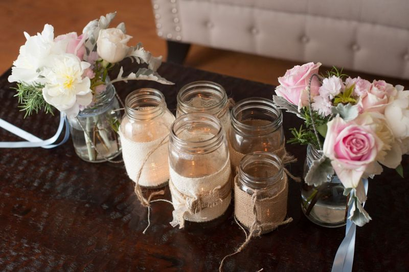 WOVEN WARMTH: Creating a rustic effect, votive candles glowed from Mason jars wrapped in burlap and twine.