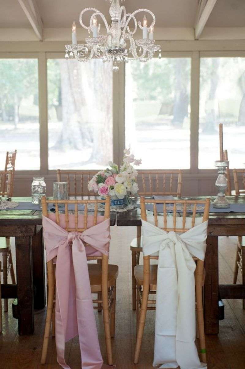 TIE THE KNOT: Coordinating pink and white silk fabric bows draped the bride and groom chairs for a subtle yet elegant addition to the dinner setting.