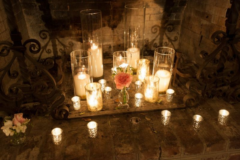 STATE OF GRACE: Mercury glass votive candles, cylinder glass candleholders, and petite flower vases brought elegance to the rural fireplace.