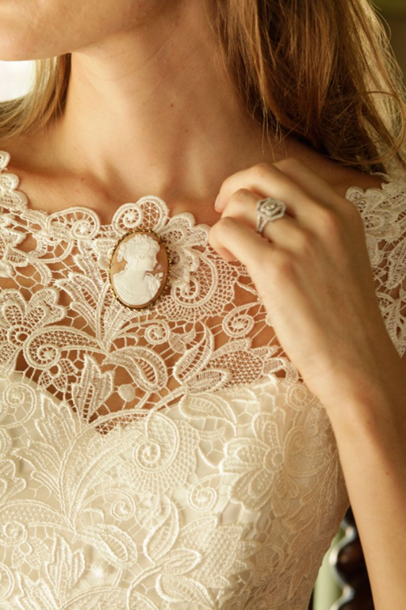 "Callie Tein's  ""Nila"" gown with bateau neckline, cap sleeves, and Italian lace overlay from Modern  Trousseau. Vintage cameo pin from Out of Hand."