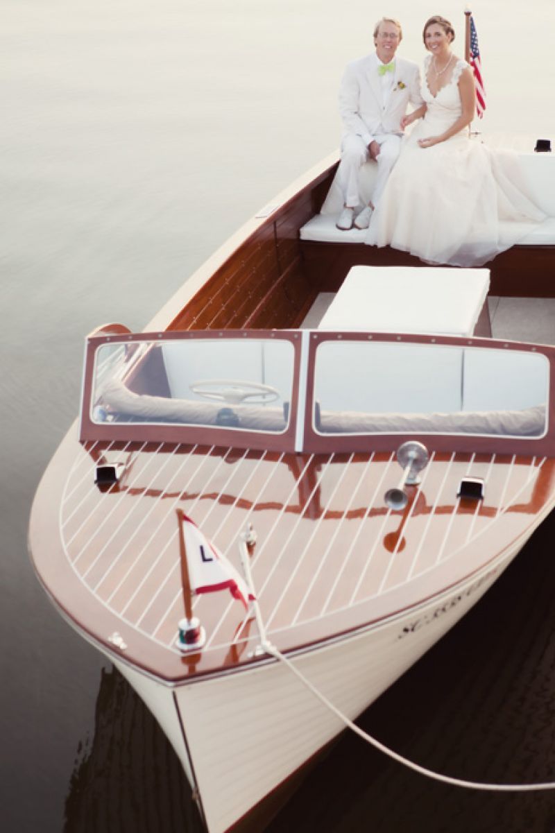 AMERICAN ROMANCE: For a couple with a shared love of boats, their 1959 wooden-hulled Lyman Boat with its classic look and patriotic spirit was the perfect choice for a getaway vehicle (and post-ceremony pictures).
