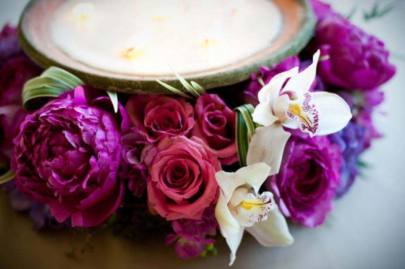 FIERY FLORA: Fuchsia peonies, pink roses, orchids, and green grasses framed neutral-colored candles to create vibrant centerpieces.