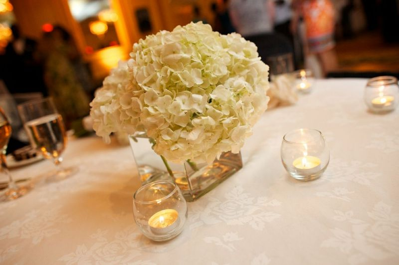 QUIET FLORA: White-on-white floral-pattern linens, hydrangea bunches, and votive candles kept reception tabletops soft and simple.