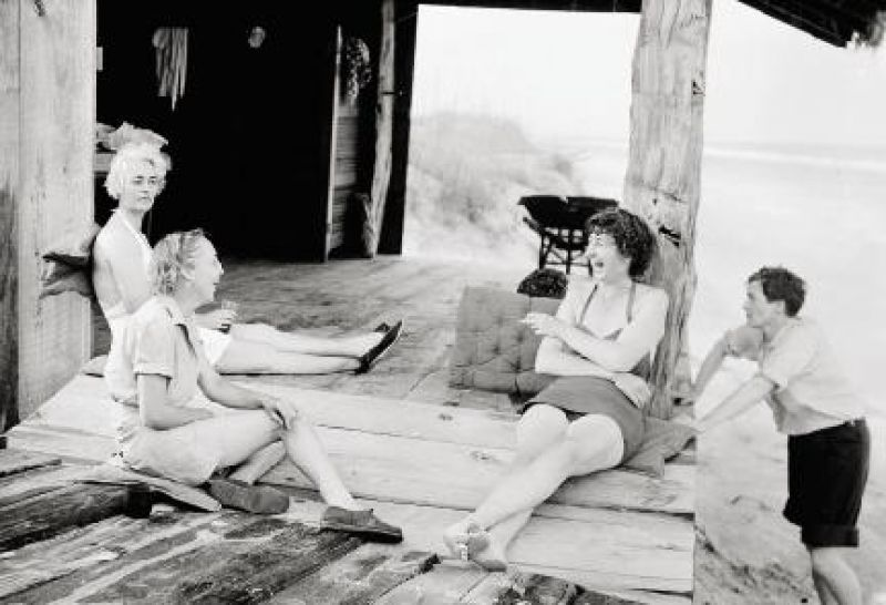 Relaxing with friends, circa 1938, at the Grass Shack at Hobcaw Beach that her former companion Barbara Donohoe had designed