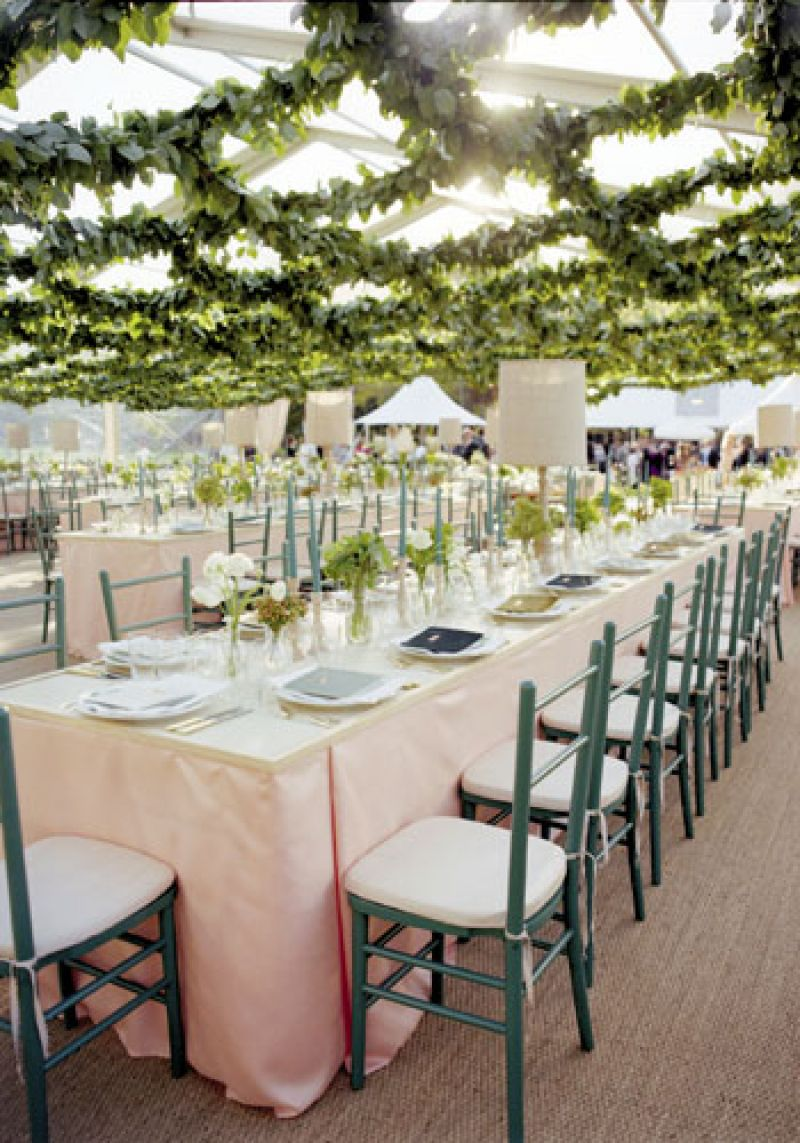 Up on High: To keep the reception from being overly formal-and to make it seem like guests were dining outside- the team at Tara Guerard Soiree covered the tent's clear ceiling in swaths of lemon leaf garland.
