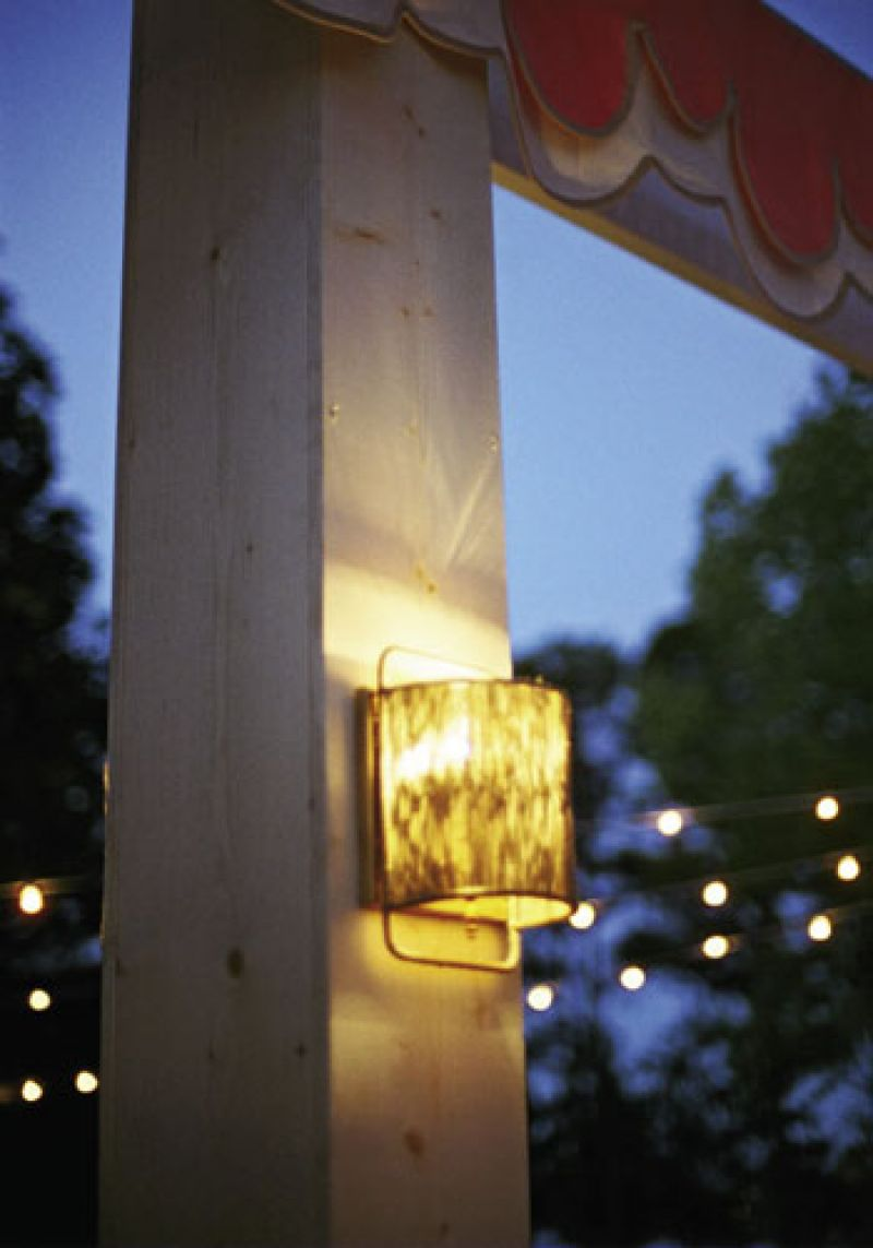 You're Glowing: Shaded sconces hung from custom-made wooden pillars that camouflaged metal tent poles.