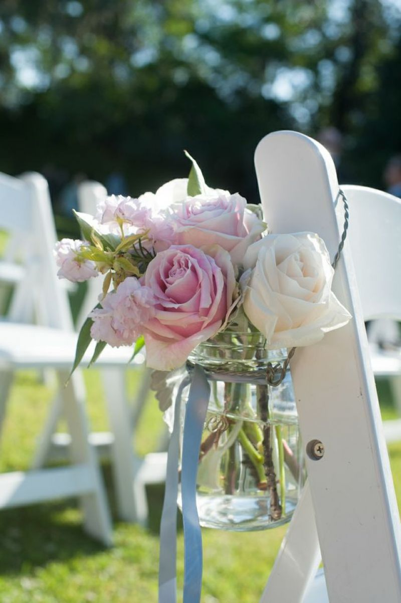 PINK 'N' BLUE: Blue ribbon-tied Mason jars filled with light pink roses, white roses, and carnations hung from chairs that lined the aisle.